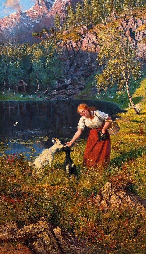 Budeie med geiter ved et vann